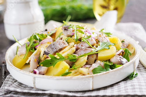 Photo Stands Ready meals Traditional salad of salted herring fillet, fresh apples, red onion and potatoes. Kosher food. Scandinavian cuisine.