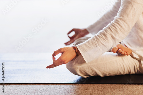 The hands of a young man yogi with closed fingers during meditation in the lotus position. Concept of yoga relaxation and meditation