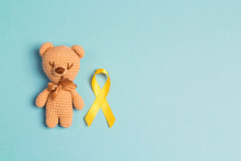 Children's Toy With A Childhood Cancer Awareness Yellow Ribbon On Blue Background.