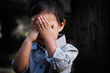 A Young Boy Of Toddler Age Covering His Face With Hands, Showing Signs Of Distress, Fear And Dissapointment.