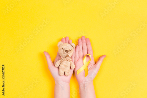 Fotografie, Obraz  Girl hands holding children's toy with a Childhood Cancer Awareness Yellow Ribbon on yellow background