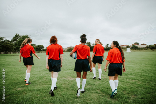 Female rugby players walking on the field