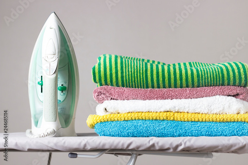 Fotografie, Obraz  Iron and a stack of towels on the ironing board, gray background