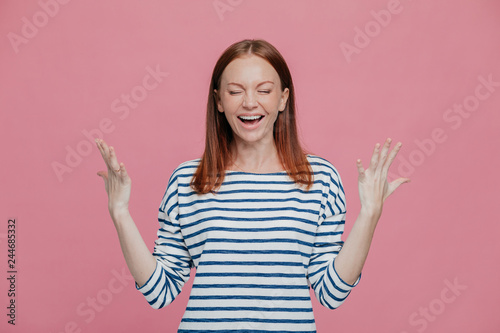 Fotografie, Obraz  Waist up shot of overjoyed pretty woman gestures with hands, laughs positively, being in high spirit, dressed in sailor striped jumper, closes eyes shut, poses against pink studio wall