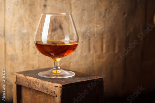 Glass of brandy near a barrel