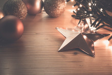 Copper Christmas Star Ornament With Fairy Lights And Rose Gold Baubles In The Background