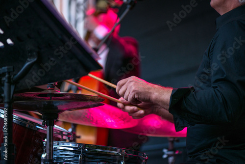 Shot of a man playing drums on stage during music festival