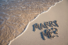 Marry Me? Marriage Proposal Message Handwritten In Smooth Sand With Wave Coming Ashore On The Beach