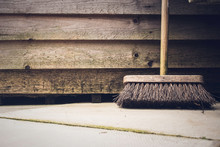 Garden Brush Leaning Against Wooden Shed On Patio