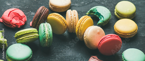 Photographie  Sweet colorful French macaroon cookies dessert variety over black background, se