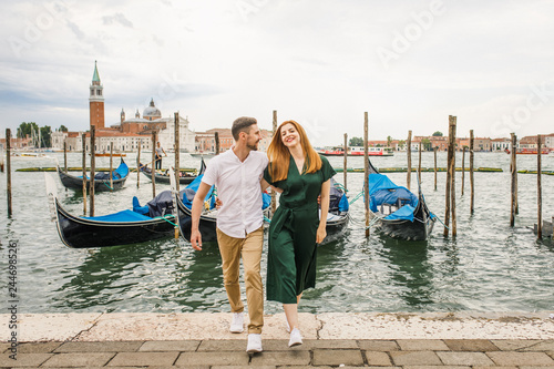 Papiers peints Gondoles Young beautiful couple girl in a green dress a man in a white shirt walk near the water overlooking the Grand Canal in Venice Italy