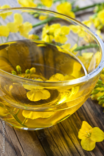 Fotobehang Kruiderij Rapesed oil and glass bowl with blossoms