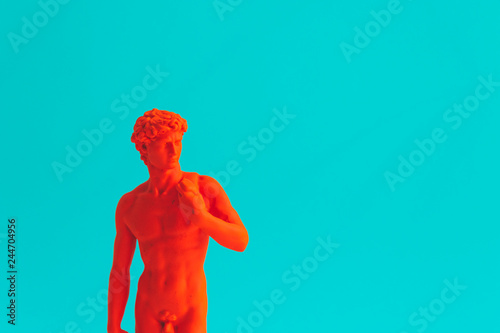 Creative concept of red neon David is a masterpiece of Renaissance sculpture created by Michelangelo. Vaporwave style. Turquoise background.