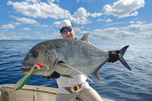 Deep Sea Fishing, Big Game Fishing. Happy  Fisherman Holding A Trevally Jack