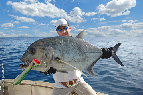 Papiers peints Peche Deep sea fishing, big game fishing. Happy fisherman holding a trevally jack