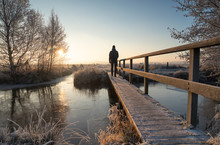 Man Walking Over A Footbridge In The Frozen, Dutch Countryside During A Winter Sunrise.