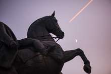 Abstract, Blurry Shot  Moon In Focus. Statue Of Knight And Horse Riding Towards Victory. New Moon And Birds In The Background Of Blue Night Sky