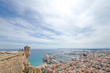 Wide angle view of Alicante, Spain from castle of Santa Barbara. Panoramic view of Postiguet beach, city and harbor. Mixed view of modern city and ruined fortress walls and towers.