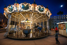 Children's Vintage Carousel At An Amusement Park In The Evening And Night Illumination. Beautiful, Bright Carousel In Alicante, Spain