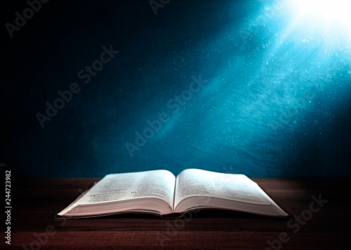 Holy Bible illuminated on a  wooden table
