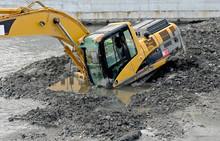 Un Escavatore Cingolato è Affondato In Un Letto Di Un Fiume Fangoso.