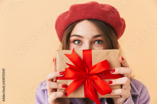 Fotografia, Obraz  Image of brunette woman 20s with long hair smiling and holding gift box, standin