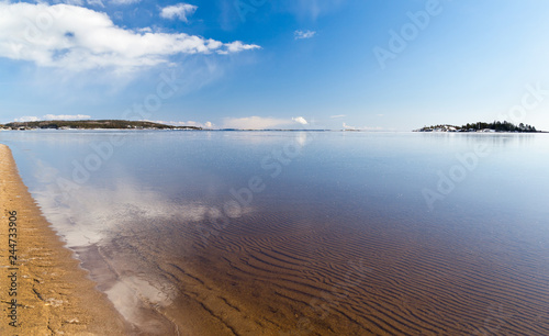 Reflection of blue sky and clouds in the freezing thin ice of Lake Ladoga in Kar Fototapet