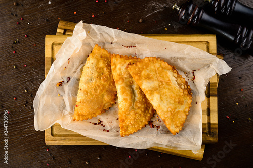 Photo hot homemade pasties on a wooden board