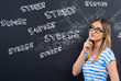 Stress theme with young woman in front of a blackboard