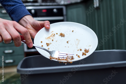 Fotografía Close up of a person throwing from a plate the leftover of buckwheat to the trash bin