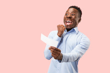 Young Afro Man With A Surprised Unhappy Failure Expression Bet Slip Onpink Studio Background. Human Facial Emotions And Betting Concept. Trendy Colors