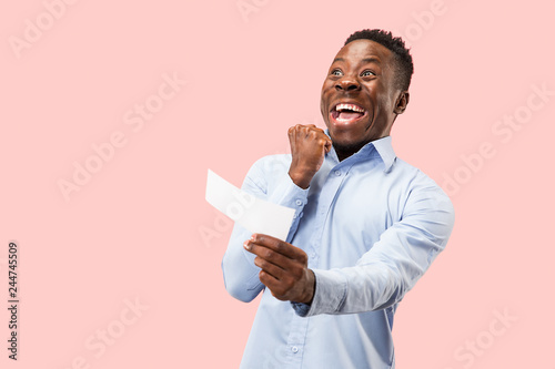 Young afro man with a surprised unhappy failure expression bet slip onpink studio background Wallpaper Mural