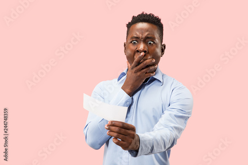 Fotografía  Young afro man with a surprised unhappy failure expression bet slip on pink studio background