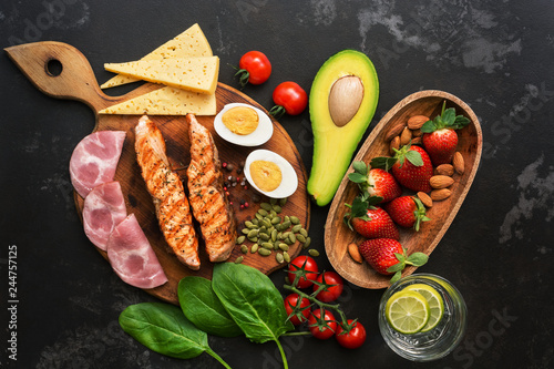 Grilled salmon with boiled egg, ham, vegetables and strawberries on a dark background Wallpaper Mural