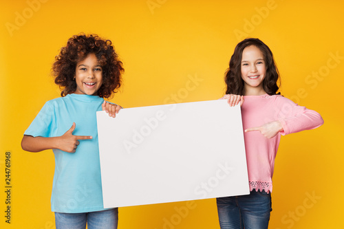 Happy girls showing blank board and pointing on it