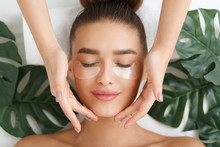 Woman With Eye Patches Having Face Massage