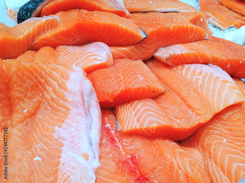 In the store (at home) in the refrigerator in the ice, fresh ready-to-cook (for sale) salmon fish is chopped (whole) Obraz na płótnie