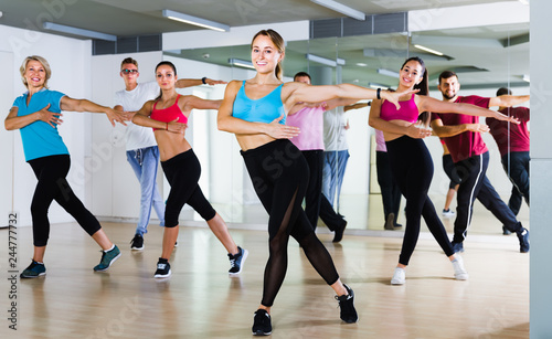 happy men and ladies dancing aerobics at lesson