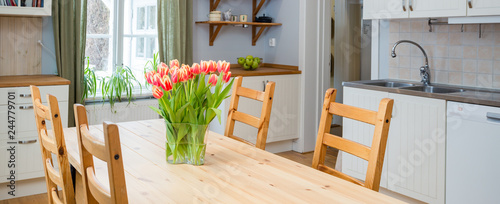 Fotomural banner tulips on the kitchen table with interior in the background