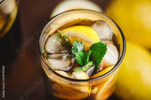 Cuba Libre cocktail with rum, cola, mint, lemon and ice in the glass on a brown Canvas Print