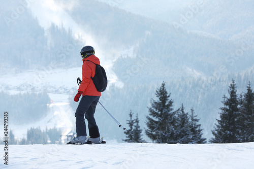 Woman skiing on snowy hill in mountains, space for text. Winter vacation