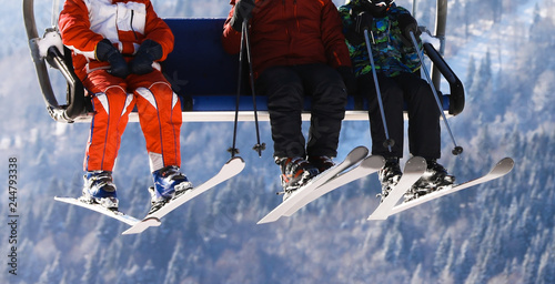 People using chairlift at mountain ski resort, closeup. Winter vacation