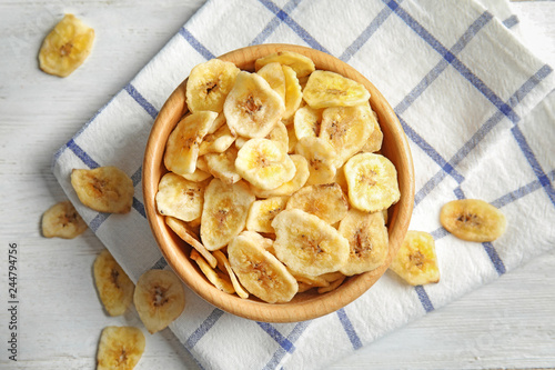 Wooden bowl with sweet banana slices on table, top view. Dried fruit as healthy snack