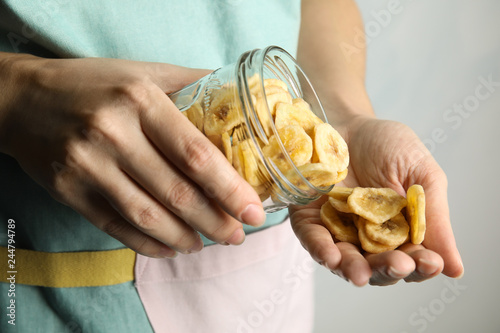 Photo sur Aluminium Confiserie Woman pouring sweet banana slices from jar to hand on light background, closeup. Dried fruit as healthy snack