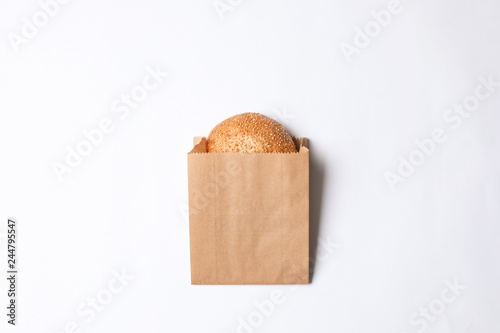 Paper bag with sesame bun on white background, top view. Space for design