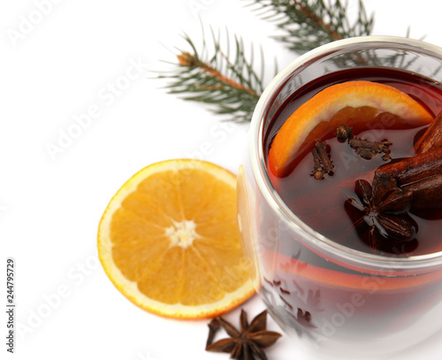 Glass of mulled wine with fir branch and orange isolated on white. Space for text