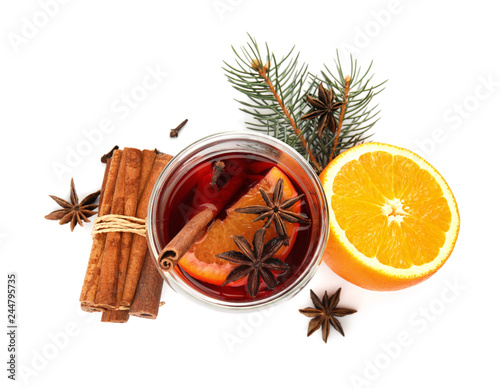 Glass of mulled wine with fir branch, cinnamon and orange isolated on white, top view
