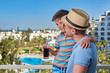 Son and dad on hotel balcony on summer holidays. Boy has glass of cola in hand.