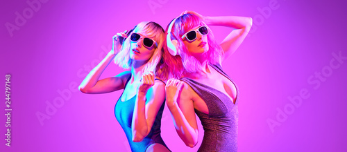 Poster Magasin de musique Fashion. Two DJ girl with Dyed Hair in Colorful neon light enjoy music, friends. Party disco 80s 90s vibes. Model woman in fashionable bodysuit, makeup. Creative art banner