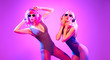 canvas print picture - Fashion. Two sexy DJ girl in Colorful neon light dance. Glamour party fitness woman with Dyed Hair in Trendy headphones. Young beautiful model enjoy nightlife. Creative art style